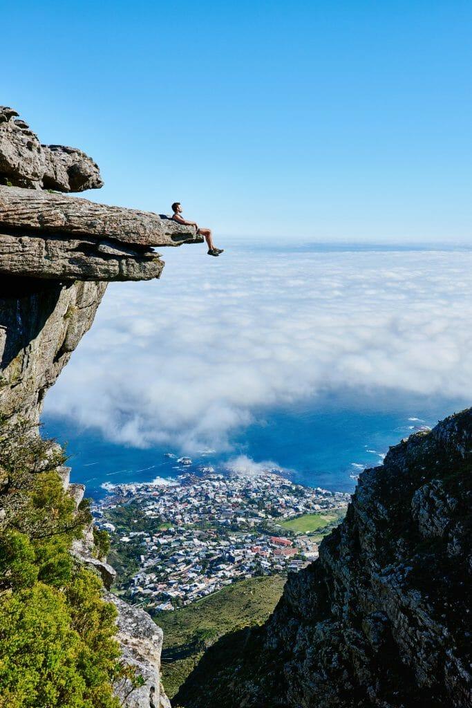 man sitting on cliff feeling free